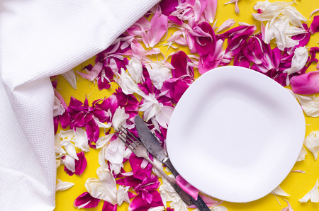 Empty plate, dish cloth, fork and knife on scattered with peony flower petals table background. Romantic lunch concept. Banco de Imagens