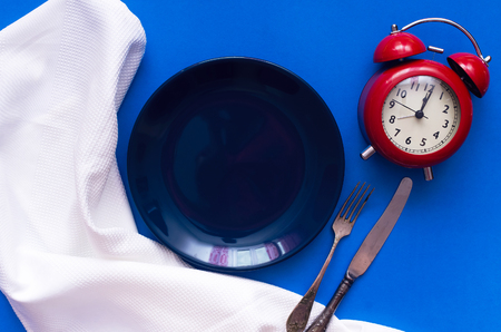 Empty plate with copy space and red alarm clock on the color kitchen table. Time to eat.