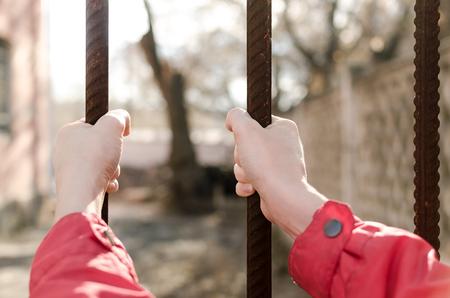 Female hands holding an iron lattice.