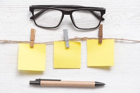 Blank paper stickers with copy space on a clothespin on a rope and eye glasses on a white table background. To do list.