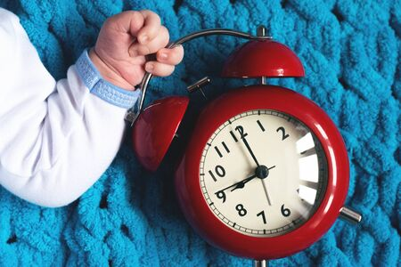 Baby hand with a red alarm clock. Time to eat.