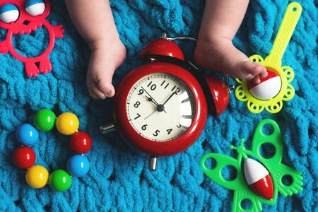 Baby feet and a red alarm clock and child toys on a blue towel background.