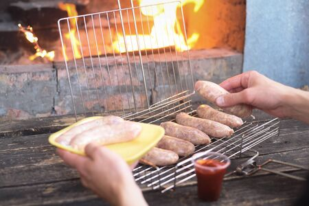 Raw barbecue sausages on a grill grate on a kitchen table background.