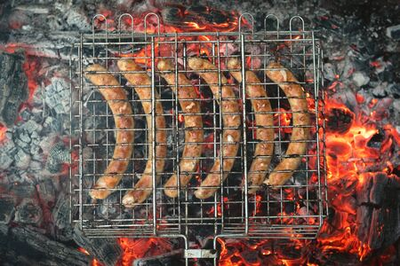 A grilled sausages on a metal grate above a burning coals background.