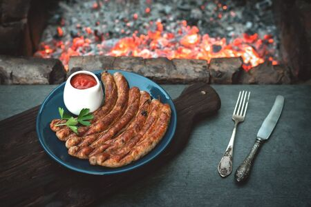 A grilled sausages on a plate on a kitchen table with a burning coals background.