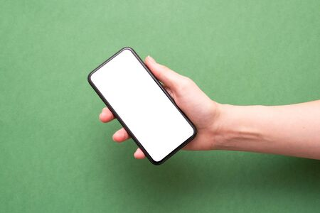 Female hand holding a blank screen mobile phone over green background.