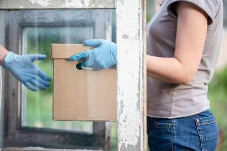 A cardboard box parcel in a courier hands close up. A delivery service in a quarantine self isolation.
