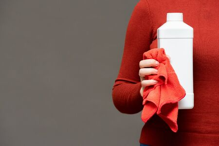 White detergent bottle and rag in female hand on gray background.