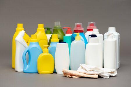 Detergent bottles on gray background.
