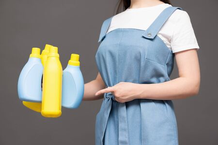 Woman with detergent bottles on gray background close up.