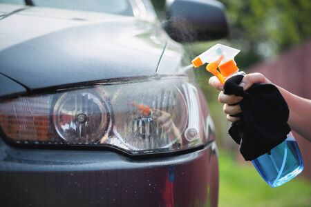 Cleaner is cleaning a car headlights with a rag close up.