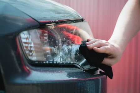 Cleaner is cleaning a car headlights with a rag close up. Imagens