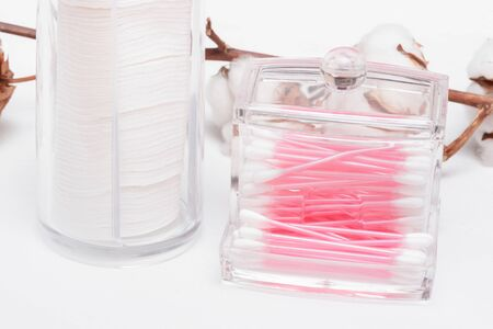Cotton wool and ear sticks in the container on a white background.