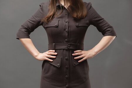 Strict woman boss is holding her hands on her belt close up on gray background. Imagens