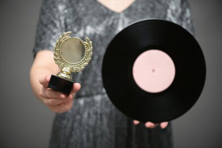 Music award ceremony concept. A singer with golden award trophy and vinyl record in hands on gray background.