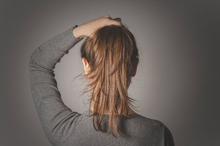 Woman holding bunch of hair in her hand isolated on gray background.