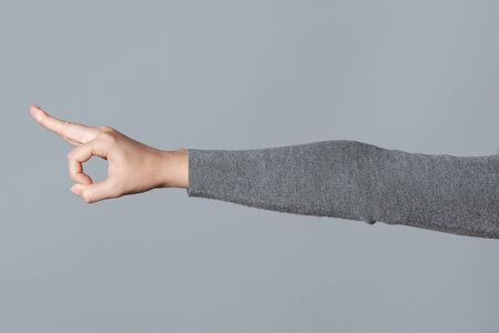 Okey gesture sign by female hand isolated on gray background.