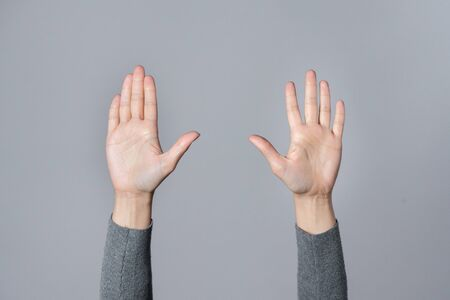 Female hands is raised up isolated on gray background. Stockfoto