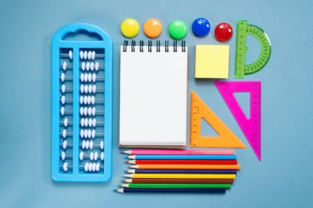 Blank page notebook and school accessories on blue flat lay background. Back to school.