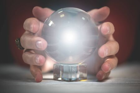 Crystal ball with mystic light within and fortune teller hands.