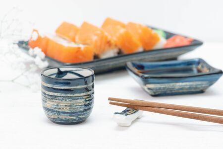 Sake drink on a sushi rolls background.