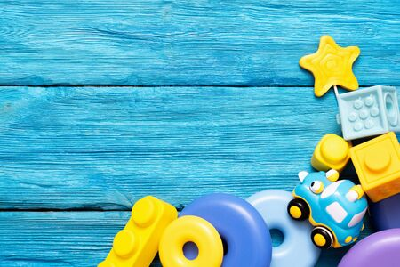 Baby toys on blue wooden table background with copy space. Children educational games.
