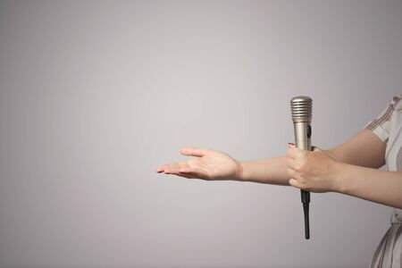 Wireless microphone in female hand isolated on gray background.