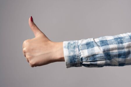 Woman showing thumbs up gesture isolated gray background.