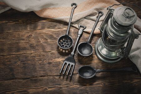 Iron fork, spoon, towel and a kerosene lamp on a brown wooden kitchen table background with copy space.
