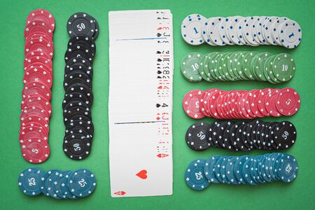 Poker chips and deck of cards on green table background. Foto de archivo