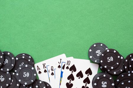 Royal Flush cards and poker chips on green flat lay background.