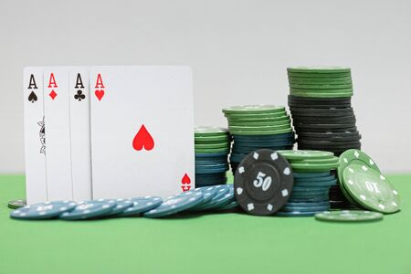 Four aces cards and poker chips on the green table background.