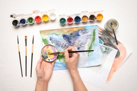 An amateur painter is drawing a picture by gouache paint on white table flat lay background close up.