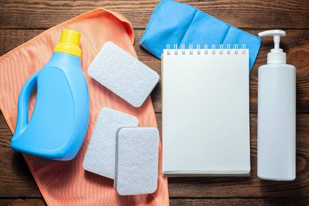 Washing supply, softener, detergent, dish cloth and blank page notepad on wooden table. Household tips mock up.