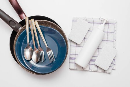 Dishes, white bottle of detergent, sponges and towel on white flat lay background. Washing up concept.