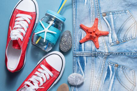 Red gum shoes, jeans shorts and cocktail jar with tube on blue flat lay background. Summer vacation background.