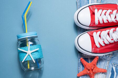 Red gum shoes, jeans shorts, starfish and cocktail jar with tube on blue flat lay background. Summer vacation background.