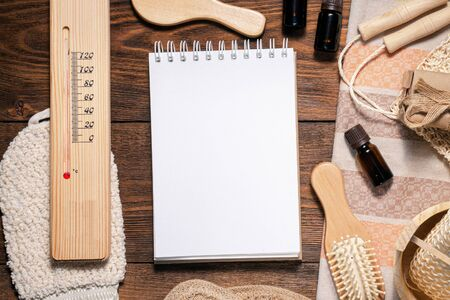 Bath house accessories and blank page notepad on brown wooden flat lay background with copy space. Hygiene concept. Bath house tips mock up. Reklamní fotografie