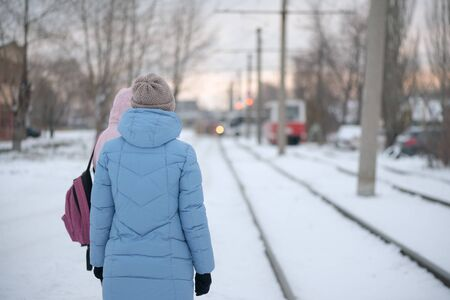 Woman waiting a tram on the tramway stop in winter.