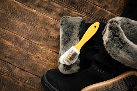 Cleaning suede boots with a shoe brush concept.