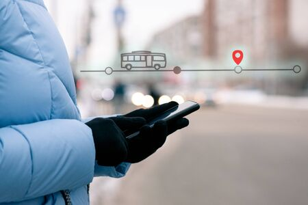 Girl tracks the location of the bus using her mobile phone online by standing at the bus stop concept.