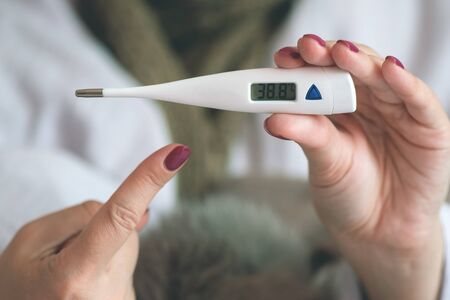 Flu sick woman is showing a thermometer with a high body temperature.