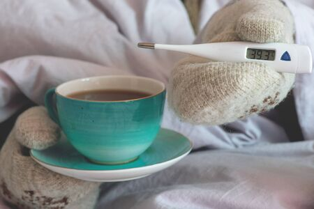 Flu sick woman with thermometer and in mittens warms up with hot tea with lemon.