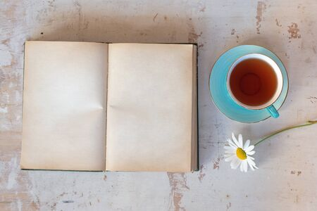 Open book with blank pages with copy space, cup of tea and daisy flower on a white wooden table background.