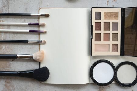 Open blank page notebook template, make up brushes and a eye shadows palette on a white wooden table flat lay background.