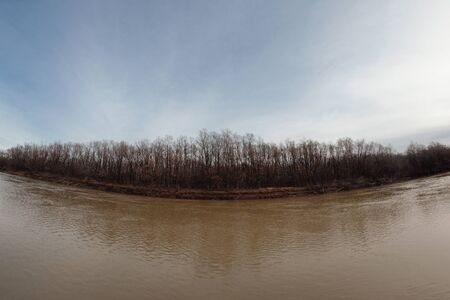 Brown water of river and autumn tree forest on a river bank background. Fisheye view.