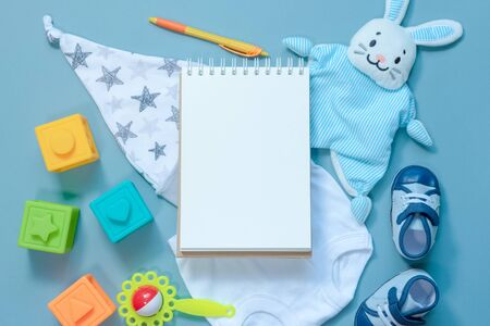 Baby toys and a blank page notebook. Newborn tips. Child game list.