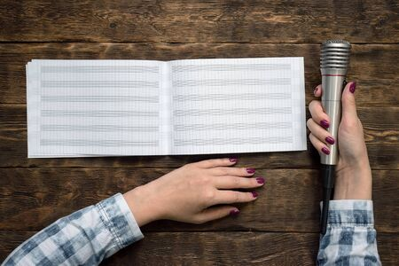 Music book and microphone in female hands on wooden table background.