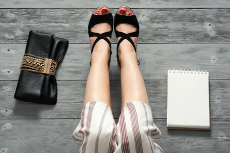 Woman legs in a high heels shoes, clutch bag and a blank page notepad. Women tips. Female tricks mock up.