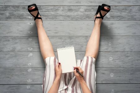 Woman legs in a high heels shoes and a blank page notepad. Women tips. Female tricks mock up. 스톡 콘텐츠